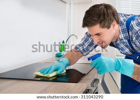 Young Happy Male Janitor Cleaning Induction Stove In Kitchen #311043290