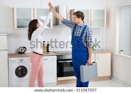 Young Woman Giving High Five To Repairman With Toolbox In Kitchen #311047097