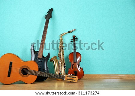 Musical instruments on turquoise wallpaper background Royalty-Free Stock Photo #311173274