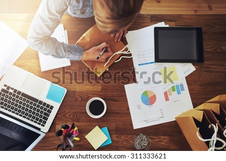 Young female entrepreneur working in a home office at her desk Royalty-Free Stock Photo #311333621