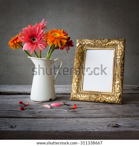 Gold vintage photo frame and flowers on wooden table over grunge background
