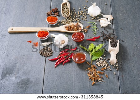 fresh and dried chili fruits, peppercorn, pepper powder, sauce and garlic, bay leaves on old black wooden table background #311358845