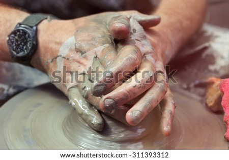 Men's hands. Potter at work. Creating dishes. Potter's wheel. Dirty hands in the clay and the potter's wheel with the product. Creation. Working potter. Centering clay. Selective focus. #311393312