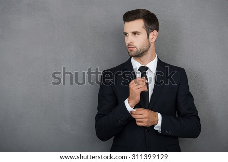 Perfect to the last detail. Handsome young businessman adjusting his sleeves while standing against grey background Royalty-Free Stock Photo #311399129