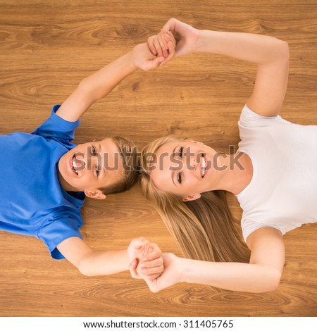 Top view of happy mother and son smiling to the camera, lying on the floor. #311405765