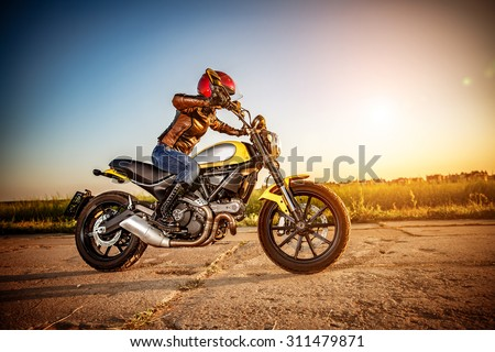 Biker girl in a leather jacket and helmet on a motorcycle #311479871