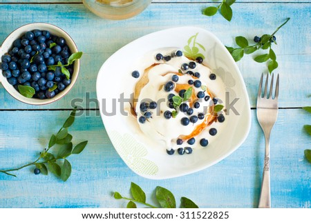 Pancakes with sour cream, blueberries and honey #311522825
