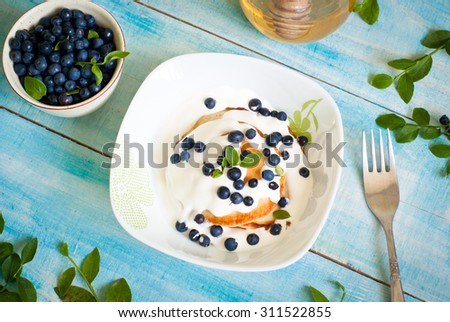 Pancakes with sour cream, blueberries and honey #311522855