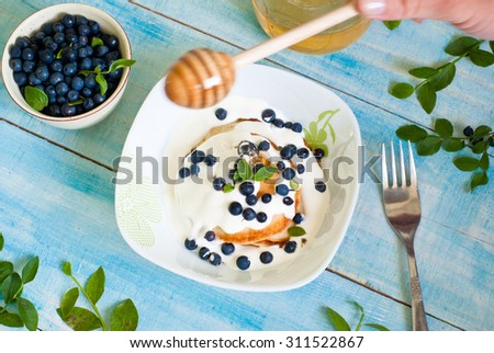 Pancakes with sour cream, blueberries and honey #311522867