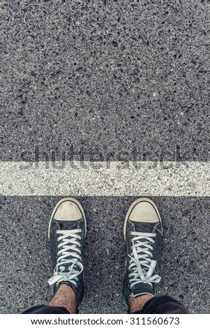 Man standing next in line on urban pavement queuing, top view of young male feet wearing modern kicks or sneakers #311560673