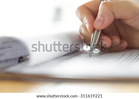 Hand with pen over application form Royalty-Free Stock Photo #311619221