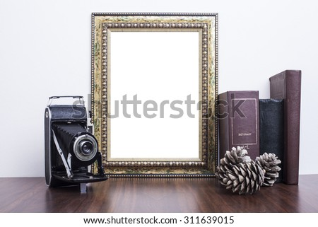 Golden Frame with old books and old camera on wood table