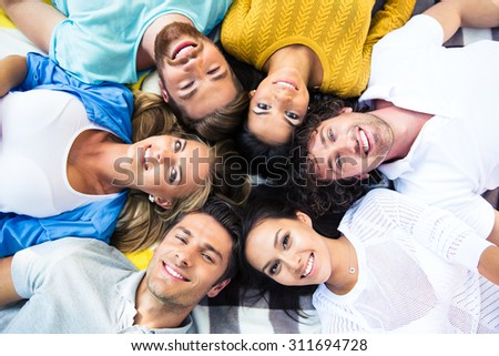 Group of cheerful friends lying together in a circle #311694728