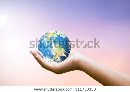 Female hands holding world on blurred sunset background with sun light. Elements of this image furnished by NASA #311753333