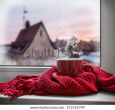 cup with a hot drink on the windowsill in the background of a winter city. Focus on the edge of the cup #311916749