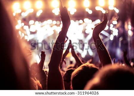 A crowd of people celebrating and partying with their hands in the air to an awesome Dj. High ISO grainy image. Royalty-Free Stock Photo #311964026