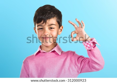 Child making Ok sign over colorful background