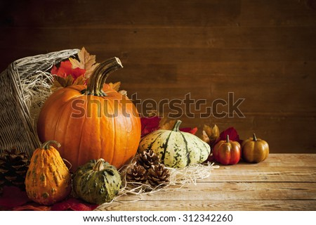 A rustic autumn still life with pumpkins and a basket on a wooden table.