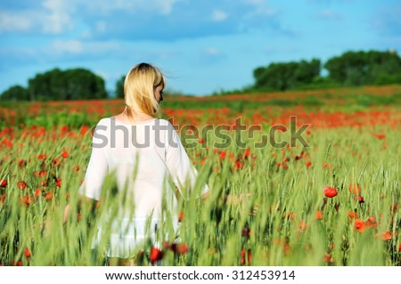 Young beautiful girl in the poppy and wheat field #312453914