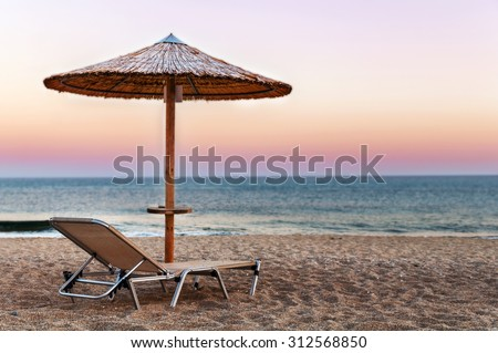 Sunbed, straw umbrella on beautiful sunset beach background #312568850
