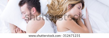 Two people in bed sleeping back to back #312671231