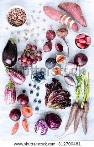 Collection of fresh purple toned vegetables and fruits on white rustic background, eggplant, beetroot, carrot, fig, plum, aubergine, cabbage, grapes, radishes, loose leaf lettuce #312700481