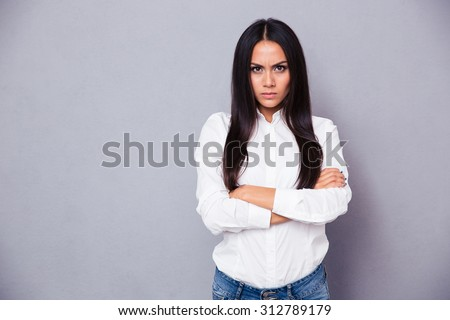 Portrait of angry woman standing with arms folded on gray background Royalty-Free Stock Photo #312789179