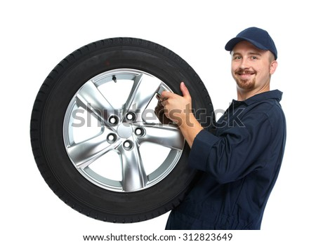 Smiling car mechanic with a tire isolated on white background. #312823649