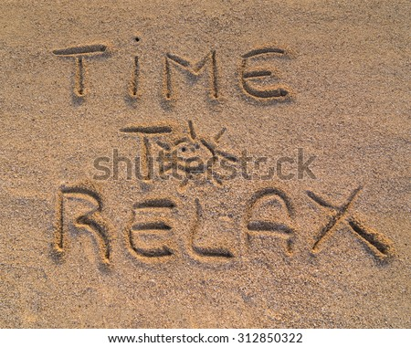 """In the picture the words on the sand """"Time to relax"""""""