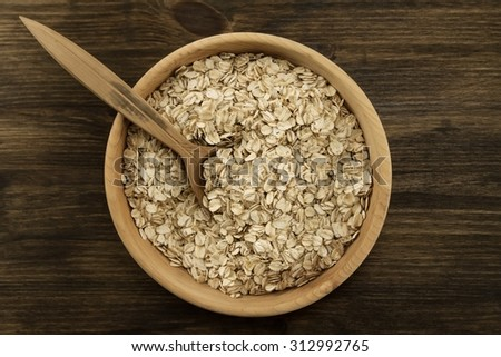 oatmeal flakes in a wooden bowl with a spoon on the table. homemade, menu, recipe, mock up #312992765