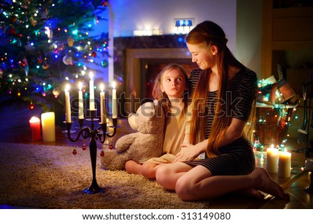 Young mother and her little daughter sitting by a fireplace in a cozy dark living room on Christmas eve #313149080