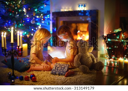 Adorable little girls opening a magical Christmas gift by a Christmas tree in cozy living room in winter #313149179