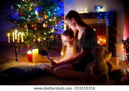 Young mother and her daughter using a tablet pc by a fireplace on warm Christmas evening #313150316