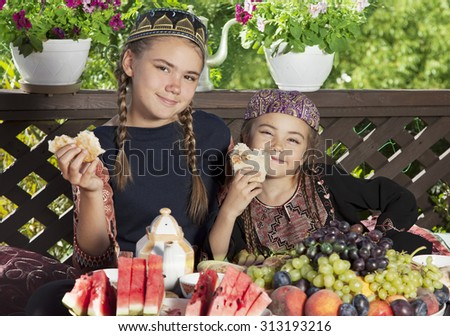 Two little girls dressed in Central Asian clothes have breakfast at chaikhana #313193216