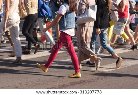 feet of young pedestrians walking on the crosswalk on summer day #313207778
