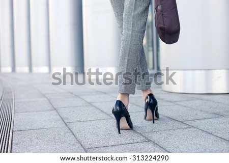 Close up of female legs of worker standing near her office. The woman is wearing formalwear and shoes on high heels. She is holding a handbag. Copy space in left side Royalty-Free Stock Photo #313224290