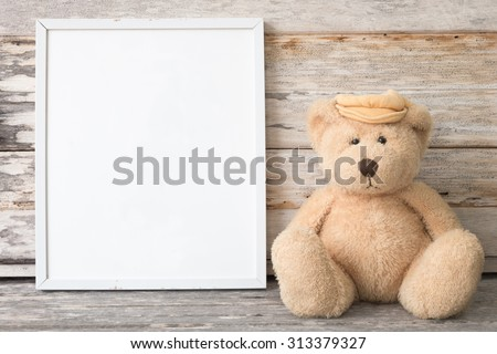 blank white picture frame and teddy Bear on wooden table