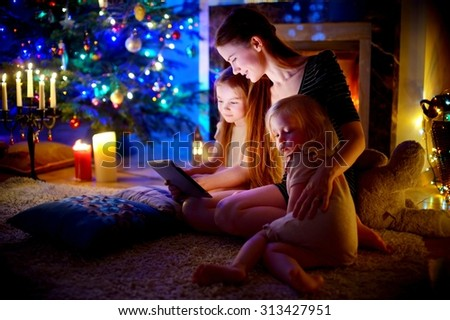 Young mother and her daughters using a tablet pc by a fireplace on warm Christmas evening #313427951