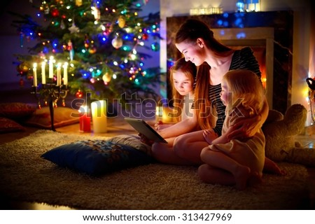 Young mother and her daughters using a tablet pc by a fireplace on warm Christmas evening #313427969
