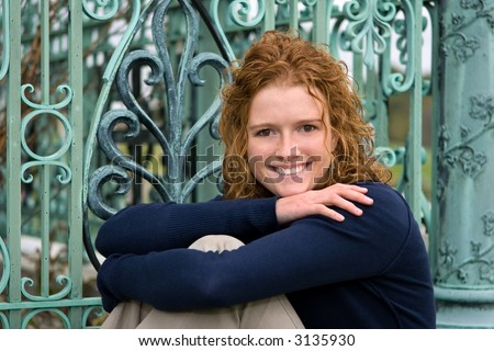 Senior Portrait of redhead female HS  student in front of weathered patina copper works.