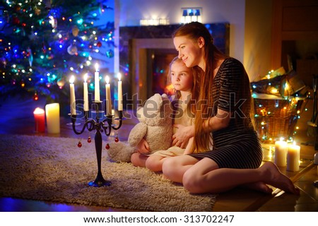 Young mother and her little daughter sitting by a fireplace in a cozy dark living room on Christmas eve #313702247