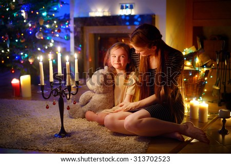 Young mother and her little daughter sitting by a fireplace in a cozy dark living room on Christmas eve #313702523