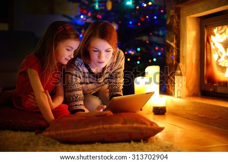 Young mother and her daughter using a tablet pc by a fireplace on warm Christmas evening #313702904