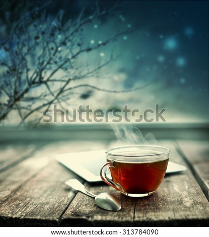 Hot tea cup on a frosty winter day window background/ Christmas holidays background/ Winter cozy background #313784090