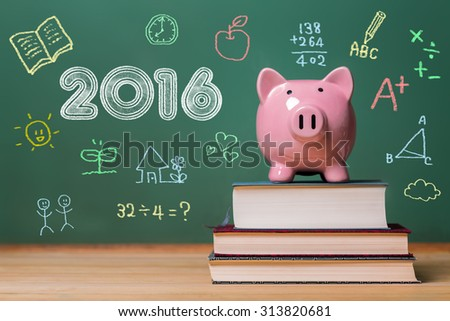 Year 2016 text with pink piggy bank on top of books with chalkboard