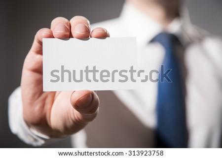 Businessman's hand showing visiting card - closeup shot #313923758