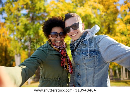 tourism, travel, people, season and technology concept - happy teenage international couple taking selfie over autumn park background