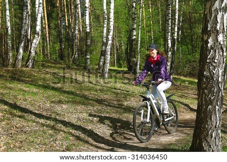 Bike riding - woman on bike in forest #314036450