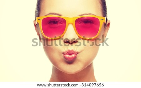 love, happiness, valentines day, face expressions and people concept - portrait of teenage girl in pink sunglasses blowing kiss #314097656
