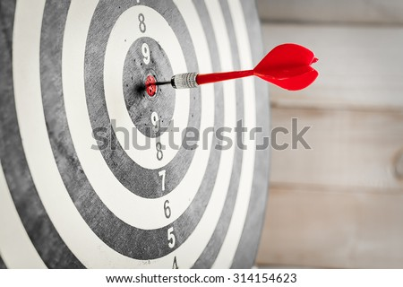 Red dart arrow hitting in the target center of dartboard #314154623